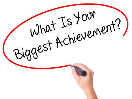 overachieving: Women Hand writing What Is Your Biggest Achievement? with black marker on visual screen. Isolated on white. Business, technology, internet concept. Stock Photo