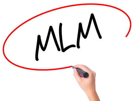 Women Hand writing  MLM (Multi-Level Marketing) with black marker on visual screen. Isolated on white. Business, technology, internet concept. Stock Photo
