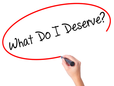 Women Hand writing What Do I Deserve? with black marker on visual screen. Isolated on white. Business, technology, internet concept. Stock Photo
