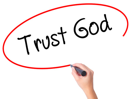 trust in god: Women Hand writing Trust God  with black marker on visual screen. Isolated on white. Business, technology, internet concept. Stock Photo
