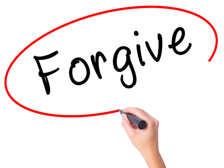 redeeming: Women Hand writing Forgive with black marker on visual screen. Isolated on white. Business, technology, internet concept. Stock Image Stock Photo