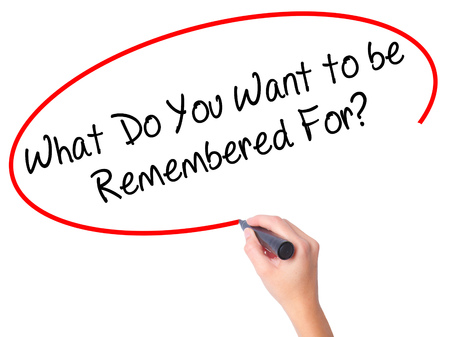 Women Hand writing What Do You Want to be Remembered For? with black marker on visual screen. Isolated on white. Business, technology, internet concept. Stock Photo