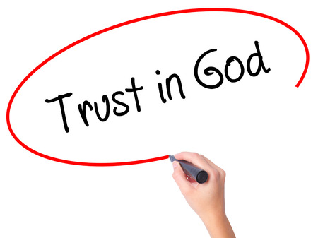 Women Hand writing Trust in God with black marker on visual screen. Isolated on white. Business, technology, internet concept. Stock Photo Stock Photo