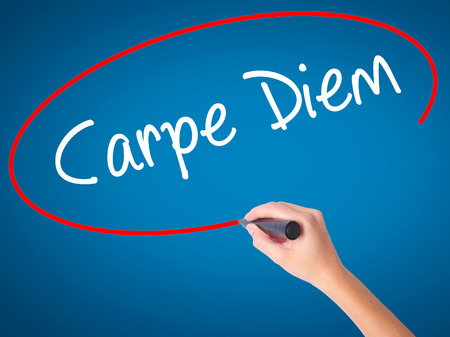 seize: Women Hand writing Carpe Diem with black marker on visual screen. Isolated on blue. Business, technology, internet concept. Stock Photo