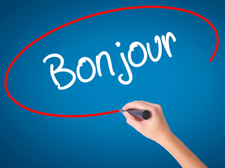 Women Hand writing Bonjour  (Good Morning in French) with black marker on visual screen. Isolated on blue. Business, technology, internet concept. Stock Photo