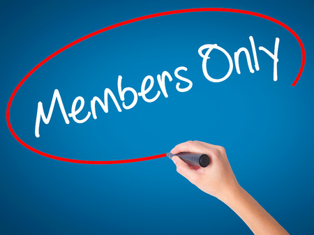 members only: Women Hand writing Members Only with black marker on visual screen. Isolated on blue. Business, technology, internet concept. Stock Photo