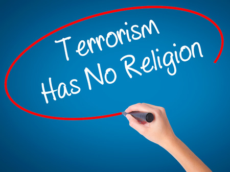 Women Hand writing Terrorism Has No Religion  with black marker on visual screen. Isolated on blue. Business, technology, internet concept. Stock Photo Stock Photo