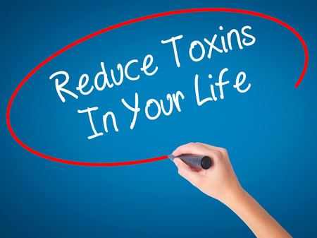 toxins: Women Hand writing Reduce Toxins In Your Life with black marker on visual screen. Isolated on blue. Business, technology, internet concept. Stock Photo