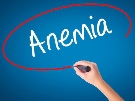 anemia: Women Hand writing Anemia  with black marker on visual screen. Isolated on blue. Business, technology, internet concept. Stock Photo Stock Photo