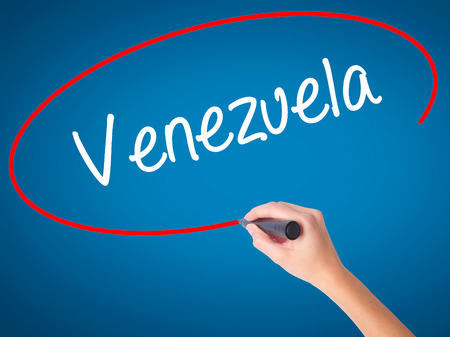Women Hand writing Venezuela with black marker on visual screen. Isolated on blue. Business, technology, internet concept. Stock Photo