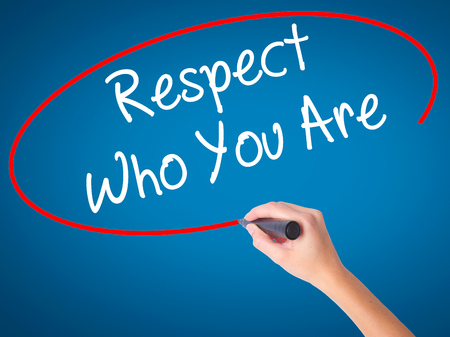 Women Hand writing Respect Who You Are with black marker on visual screen. Isolated on blue. Business, technology, internet concept. Stock Photo