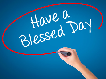 Women Hand writing Have a Blessed Day  with black marker on visual screen. Isolated on blue. Business, technology, internet concept. Stock Photo