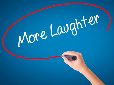 Women Hand writing More Laughter with black marker on visual screen. Isolated on blue. Business, technology, internet concept. Stock Photo
