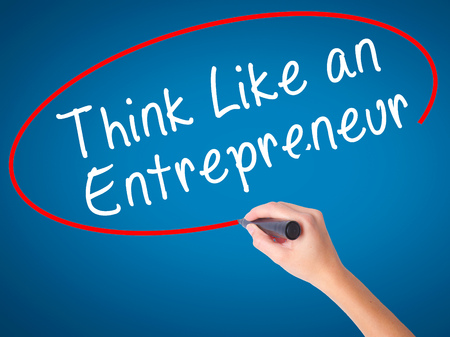 Women Hand writing Think Like an Entrepreneur with black marker on visual screen. Isolated on blue. Business, technology, internet concept. Stock Image