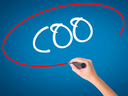 coo: Women Hand writing COO (Chief Operating Officer) with black marker on visual screen. Isolated on blue. Business, technology, internet concept. Stock Photo