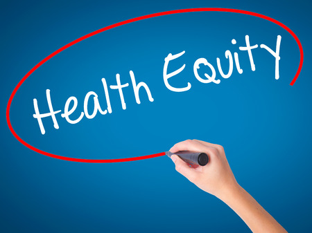 health equity: Women Hand writing Health Equityt with black marker on visual screen. Isolated on blue. Business, technology, internet concept. Stock Photo