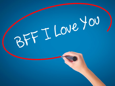 postit note: Women Hand writing BFF I Love You with black marker on visual screen. Isolated on blue. Business, technology, internet concept.