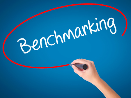 benchmarking: Women Hand writing Benchmarking  with black marker on visual screen. Isolated on blue. Business, technology, internet concept. Stock Photo