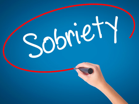 sobriety: Women Hand writing Sobriety with black marker on visual screen. Isolated on blue. Business, technology, internet concept. Stock Photo