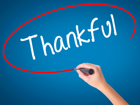 Women Hand writing Thankful  with black marker on visual screen. Isolated on blue. Business, technology, internet concept. Stock Photo