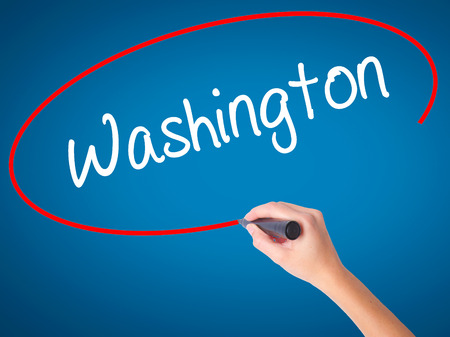 Women Hand writing Washington  with black marker on visual screen. Isolated on blue. Business, technology, internet concept. Stock Photo