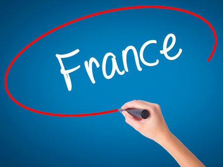 Women Hand writing France with black marker on visual screen. Isolated on blue. Business, technology, internet concept. Stock Photo Stock Photo