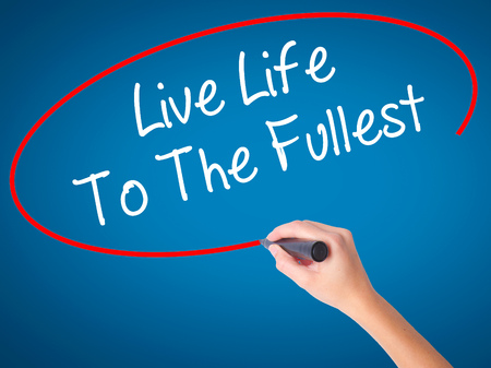 seize: Women Hand writing Live Life To The Fullest with black marker on visual screen. Isolated on blue. Business, technology, internet concept. Stock Photo