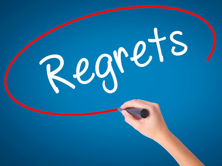 Women Hand writing  Regrets with black marker on visual screen. Isolated on blue. Business, technology, internet concept. Stock Photo