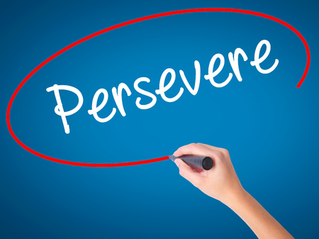Women Hand writing Persevere with black marker on visual screen. Isolated on blue. Business, technology, internet concept. Stock Photo