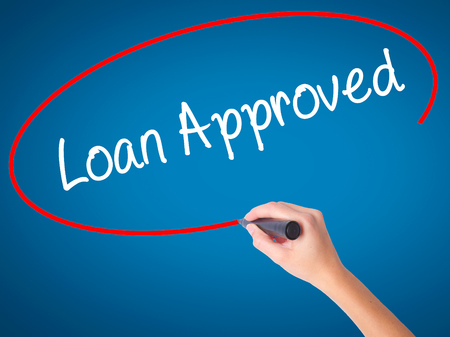Women Hand writing Loan Approved with black marker on visual screen. Isolated on blue. Business, technology, internet concept. Stock Photo Stock Photo