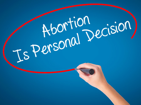 Women Hand writing Abortion Is Personal Decision with black marker on visual screen. Isolated on blue. Business, technology, internet concept. Stock Photo Stock Photo
