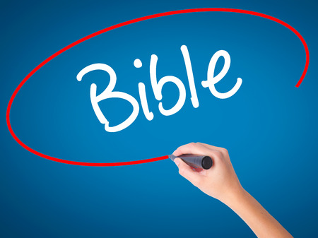 vangelo aperto: Women Hand writing Bible with black marker on visual screen. Isolated on blue. Business, technology, internet concept. Stock Photo Archivio Fotografico