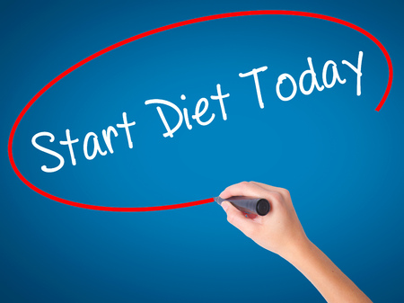 Women Hand writing Start Diet Today  with black marker on visual screen. Isolated on blue. Business, technology, internet concept. Stock Photo Stock Photo