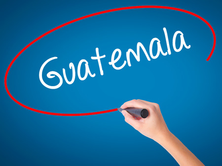 Women Hand writing Guatemala  with black marker on visual screen. Isolated on blue. Business, technology, internet concept. Stock Photo