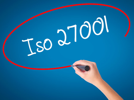Women Hand writing Iso 27001  with black marker on visual screen. Isolated on blue. Business, technology, internet concept. Stock Photo