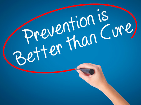 cure prevention: Women Hand writing Prevention is Better than Cure with black marker on visual screen. Isolated on blue. Business, technology, internet concept. Stock Image