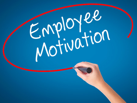 induce: Women Hand writing Employee Motivation with black marker on visual screen. Isolated on blue. Business, technology, internet concept. Stock  Photo