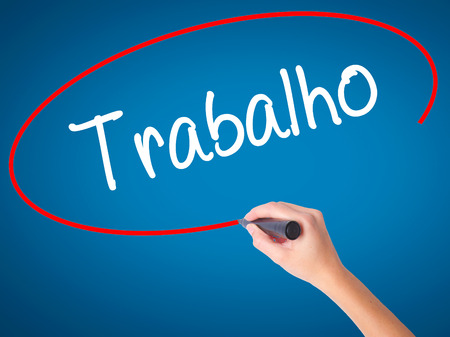Women Hand writing Trabalho (Work in Portuguese) with black marker on visual screen. Isolated on blue. Business, technology, internet concept. Stock Photo Stock Photo