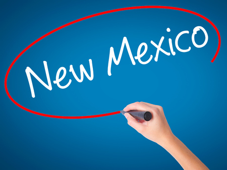 Women Hand writing New Mexico with black marker on visual screen. Isolated on blue. Business, technology, internet concept. Stock Photo