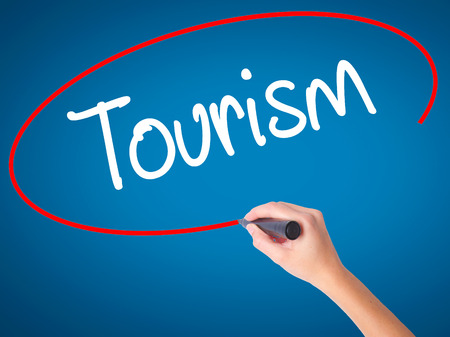 Women Hand writing Tourism  with black marker on visual screen. Isolated on blue. Business, technology, internet concept. Stock Photo