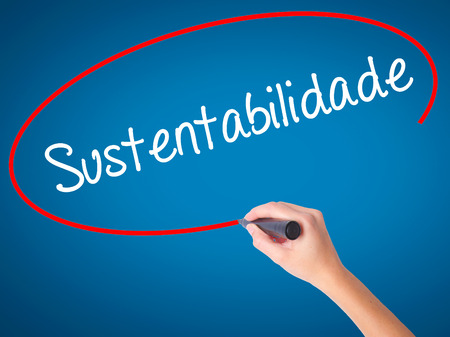 Women Hand writing Sustentabilidade (In portuguese - Sustainability) with black marker on visual screen. Isolated on blue. Business, technology, internet concept. Stock Photo Stock Photo