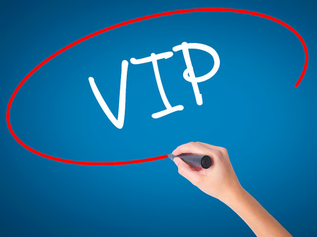Women Hand writing  VIP with black marker on visual screen. Isolated on blue. Business, technology, internet concept. Stock Photo