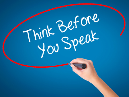 Women Hand writing Think Before You Speak with black marker on visual screen. Isolated on blue. Business, technology, internet concept. Stock Photo
