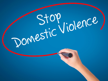 Women Hand writing  Stop Domestic Violence with black marker on visual screen. Isolated on blue. Business, technology, internet concept. Stock Photo Stock Photo
