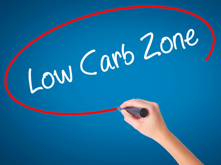 nonfat: Women Hand writing Low Carb Zone with black marker on visual screen. Isolated on blue. Business, technology, internet concept. Stock Photo