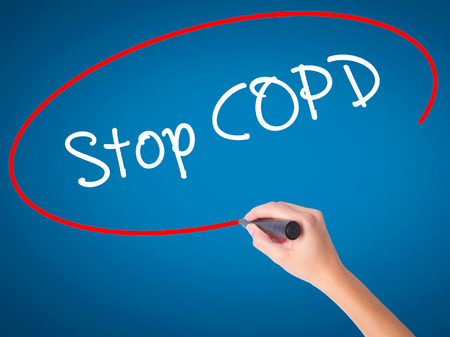 Women Hand writing Stop COPD with black marker on visual screen. Isolated on blue. Business, technology, internet concept. Stock Photo