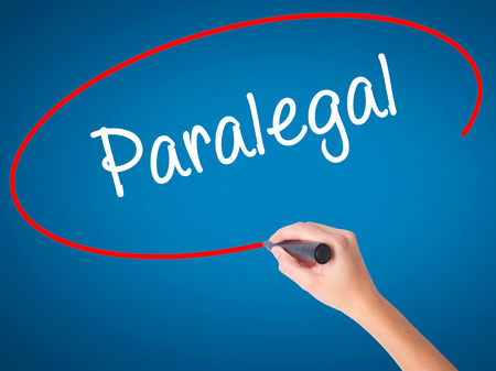paralegal: Women Hand writing Paralegal with black marker on visual screen. Isolated on blue. Business, technology, internet concept. Stock Photo