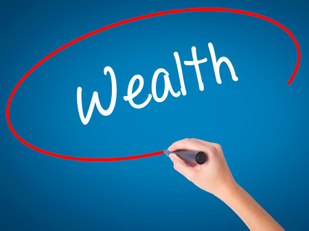 Women Hand writing Wealth with black marker on visual screen. Isolated on blue. Business, technology, internet concept. Stock Photo