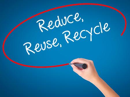 recycle reduce reuse: Las mujeres Escritura de la mano reduce la reutilización recicla con marcador negro en la pantalla visual. Aislado en azul. Negocios, la tecnología, el concepto de internet. Foto de stock Foto de archivo