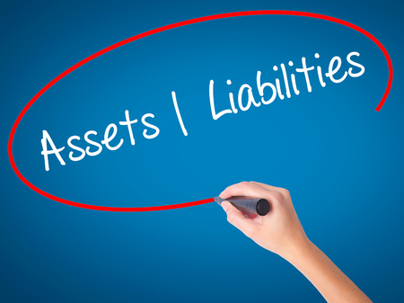 Women Hand writing Assets Liabilities with black marker on visual screen. Isolated on blue. Business, technology, internet concept. Stock Photo